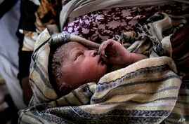 A new born baby girl lays in her mothers' arms right after being born onboard a Spanish rescue vessel on the Mediterranean Sea,  Sept. 6, 2017. A rescued woman from Ghana has given birth to a girl immediately after being rescued while trying to cross
