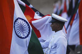 An Indian Navy soldier holds an Indian national flag during a dress rehearsal ahead of Navy Day celebrations in Mumbai, December 2, 2011.