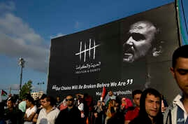 FILE - Protesters hold a banner with a picture of jailed Palestinian uprising leader Marwan Barghouti  during a rally supporting Palestinian prisoners in Israeli jails on a hunger strike, in the West Bank city of Ramallah, May 3, 2017.