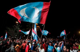 Opposition party supporters cheer and wave their party flags after Mahathir Mohamad claims the opposition party wins the General Election, broadcast on a large screen at a field in Kuala Lumpur, Malaysia, May 9, 2018.