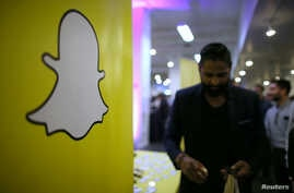 FILE -  The logo of messaging app Snapchat is seen at a booth at TechFair LA, a technology job fair, in Los Angeles, California.