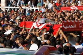 Relatives and colleagues carry the coffin of a Tunisian policeman Socrate Cherni during a funeral as they proceed to Kef Cemetery in Kef, 168 km (104 miles) from Tunis, Oct.24, 2013.