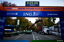 Workers install a platform during the ceremonial painting of the New York City Marathon blue line at Central Park in New York, October 30, 2013. More than 45,000 runners will race through the streets of New York City on Sunday. REUTERS/Eduardo Munoz