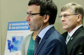 Washington Attorney General Bob Ferguson, center, talks to reporters Sept. 28, 2017, in Seattle, as Seattle City Attorney Pete Holmes, right, looks on.