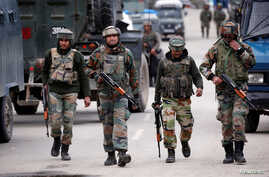 FILE - Indian army soldiers patrol a street near a site of a gunbattle between Indian security forces and suspected militants in Khudwani village of South Kashmir's Kulgam district, April 11, 2018.