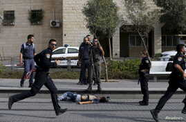 Israeli police officers stand near the body of an alleged Palestinian assailant at the scene of a stabbing in Pisgat Zeev, an Israeli settlement on the northern edge of Jerusalem, Oct. 12, 2015.