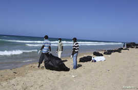 FILE - Public service workers bag bodies of migrants that drowned off Tripoli's coast, Aug. 25, 2014.