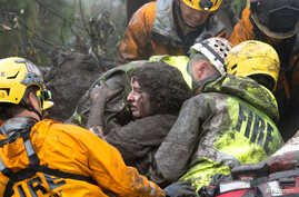 Emergency personnel carry a woman rescued from a collapsed house after a mudslide in Montecito, California, U.S. Jan. 9, 2018.