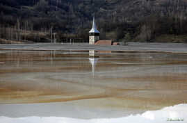 The old church of Geamana village is partially submerged by polluted water tainted with cyanide and other chemicals near Rosia Montana, central Romania, March 24, 2014.