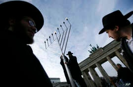 FILE - Rabbis install a giant Hanukkah Menorah at the launch of the eight-day Jewish Festival of Lights, named Hanukkah, in front of the Brandenburg Gate in Berlin, Germany.