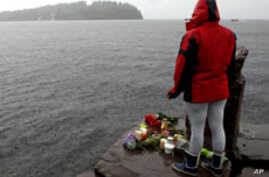 A woman stands on the shore in front of Utoeya island, northwest of Oslo, July 24, 2011