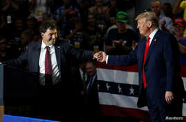 Ohio Senator Troy Balderson shakes hands with U.S. President Donald Trump during a Make America Great Again rally in Olentangy Orange High School in Lewis Center, OH, Aug. 4, 2018.