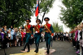 Schoolchildren watch as servicemen carry a flag of the Russia-backed self-proclaimed separatist Donetsk republic, at a ceremony on the first day of school in Donetsk, Ukraine, Sept. 1, 2017. Ukrainian government and pro-Russia separatists in eastern ...