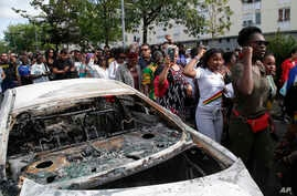 People walk past a charred car during a march after police shot a driver apparently trying to avoid an identity check earlier this week, July 5, 2018 in Nantes, western France.