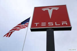 FILE - The Tesla logo is visible atop a charging station in Salt Lake City, Utah, Sept. 28, 2017.