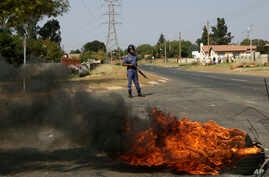 A police officer stands on a barricaded street as tires burn during a protest in Ennerdale town township, Johannesburg, South Africa, May 11, 2017.