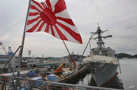 FILE - In this May 27, 2014 photo, Japan's military flag, the Rising Sun Flag, flutters on the Japan Maritime Self-Defense Force tank landing ship JS Kunisaki anchored in Yokosuka near Tokyo, getting ready for participating in the Pacific Partnership