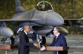 With an F-16 fighter in the background, U.S. President Barack Obama and Poland's President Bronislaw Komorowski (R) shake hands upon Obama's arrival at Chopin Airport in Warsaw, June 3, 2014.