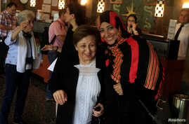 FILE - Nobel Peace Prize winners Shirin Ebadi of Iran, left, and Tawakkol Karman of Yemen react while arriving to a news conference as part of the Nobel Women's Initiative, to gather a first-hand account of the ongoing violence against women land def