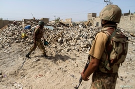 FILE - Pakistani soldiers stand near the debris of a house which was destroyed during a military operation against Taliban militants in the  town of Miranshah in North Waziristan, July 9, 2014.