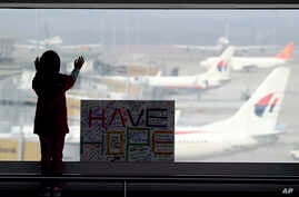 A girl stands next to a sign board at Kuala Lumpur International Airport in Sepang, Malaysia, March 10, 2014.