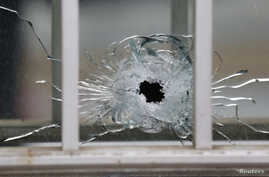 A bullet's impact is seen on a window at the scene after a shooting at the Paris offices of Charlie Hebdo, a satirical newspaper, Jan. 7, 2015.