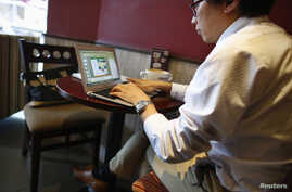 A man works on his computer inside a coffee shop in downtown Shanghai September 25, 2013. Facebook Inc and Twitter face a daunting task in China, if access to their social networks is unblocked, as they would be up against deeply entrenched domestic