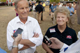 In this Thursday, Aug. 16, 2012 photograph, Rep. Todd Akin, R-Mo., and his wife Lulli, talk with reporters while attending the Governor's Ham Breakfast at the Missouri State Fair in Sedalia, Mo.