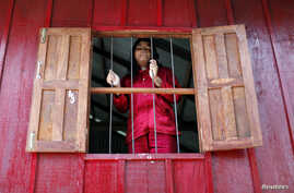 "Former garment factory worker Channa Prak, 20, who is an acid attack victim, looks out of a window at a secure shelter run by non-profit organization ""Cambodia Acid Survivors Charity"" outside Phnom Penh, July 7, 2010."