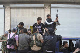 This citizen journalism image provided by Edlib News Network (ENN), purports to show Syrian rebels gathered on their vehicle in the northern town of Kfar Nebel, in Idlib province, Syria, June 5, 2012.