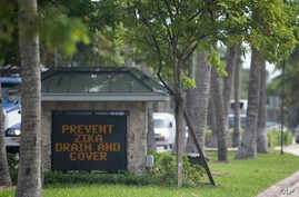 A sign at the entrance of town, reminds residents to drain or cover standing water to prevent mosquitos from reproducing, , in Key Biscayne, Fla., Aug. 17, 2016.
