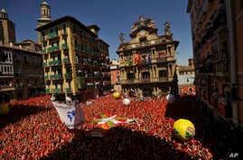 """People gather for the launch of a firework rocket, known as the """"Chupinazo"""", to celebrate the official opening of the 2016 San Fermin festival, in Pamplona, northern Spain, July 6, 2016."""