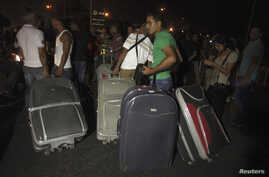 Passengers carrying their baggage try to pass, after the main road leading to Beirut airport was blocked by relatives of the 11 Lebanese Shi'ite pilgrims that were abducted in Syria, August 15, 2012.
