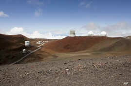 FILE - Observatories sit atop Hawaii's Mauna Kea, near Hilo, Hawaii, August 31, 2015. Hearings are still underway for a permit to build what would be one of the world's largest telescopes in Hawaii, but a group challenging the project is already appe