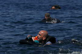 A Syrian refugee holding a baby in a lifetube swims towards the shore after their dinghy deflated some 100m away before reaching the Greek island of Lesbos, Sept. 13, 2015.