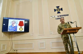 FILE - Deputy Head of the Security Service of Ukraine SBU Viktor Kononenko (R) speaks during a press conference as a picture of Kyrylo Vyshynsky, a detained journalist, is seen on a screen in Kyiv, May 15, 2018.