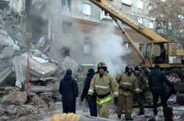 This photo provided by the Russian Emergency Situations Ministry taken from TV footage shows Emergency Situations employees working at the scene of a collapsed section of an apartment building, in Magnitigorsk, Russia, Dec. 31, 2018.