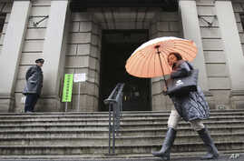 A woman walks past in front of Bank of Japan, Jan. 29, 2016. The Bank of Japan on Friday introduced a negative interest policy for the first time, seeking to shore up a stumbling recovery in the world's third-largest economy.
