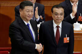 Chinese Premier Li Keqiang, right, shakes hands with Chinese President Xi Jinping, after he is re-elected premier for another term, at the sixth plenary session of the National People's Congress at the Great Hall of the People in Beijing, March 18, 2