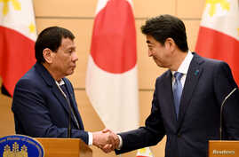 Philippines President Rodrigo Duterte shakes hands with Japanese Prime Minister Shinzo Abe at the end of their signing ceremony and joint remarks at Abe's official residence in Tokyo, Oct. 30, 2017.
