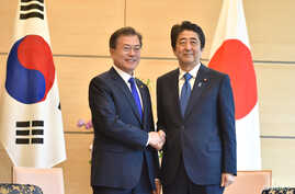 South Korea's President Moon Jae-in, left, shakes hands with Japan's Prime Minister Shinzo Abe, right, before their meeting at Abe's official residence in Tokyo, Japan, May 9, 2018.