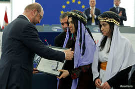 Nadia Murad Basee Taha (C) and Lamiya Aji Bashar (R), both Iraqi women of the Yazidi faith receive their 2016 Sakharov Prize from European Parliament President Martin Schulz (L) during an award ceremony at the European Parliament in Strasbourg, Franc