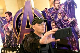 """CinemaCon attendee Luis Saint Amant, of Argentina, takes a selfie in front of an advertisement for the upcoming film """"Avengers: Endgame,"""" on the first day of CinemaCon 2019, the official convention of the National Association of Theatre Owners (NATO)"""
