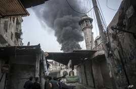 Syrian rebels watch smoke rises as government artillery strike in Jedida district of Aleppo, Syria. November, 2012. (AP)