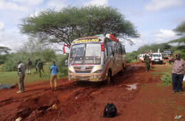 Kenyan security forces and others gather around the scene on an attack on a bus about 50 kilometers (31 miles) outside the town of Mandera, near the Somali border in northeastern Kenya, Saturday, Nov. 22, 2014.