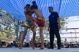 Nanthawat Pomsod (C), 11, who is a child boxer, fights Kritthonglek Sitkritthongkam (L) during a boxing match at a temple in Buriram province, Thailand, Feb. 2, 2018.