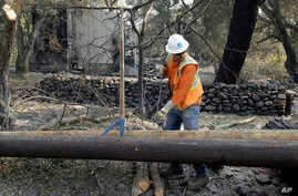 FILE - In this Oct. 18, 2017, photo, a Pacific Gas & Electric worker replaces power poles destroyed by wildfires in Glen Ellen, Calif. The National Weather Service has issued warnings for increased fire risk across a swath of northern California on O