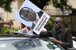A protester holds a poster showing support for ousted Zimbabwean Vice President Emmerson Mnangagwa, in Harare, Zimbabwe, Nov. 18, 2017.
