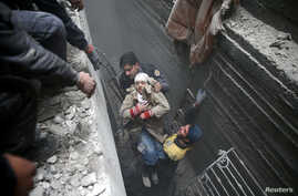 Syria Civil Defence members help an unconscious woman from a shelter in the besieged town of Douma, Eastern Ghouta, Damascus, Syria, Feb. 22, 2018.