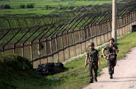 South Korean army soldiers patrol through the military wire fence in Paju, near the border with North Korea, South Korea, June 30, 2014.